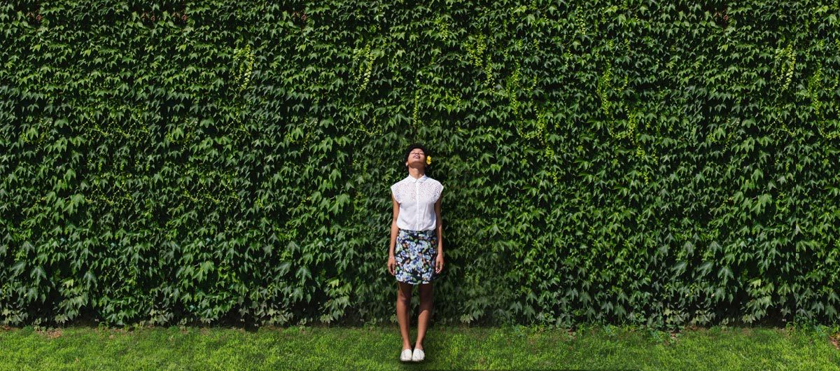 Woman standing by hedge